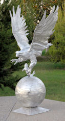 large flying eagle statue on ball with fish